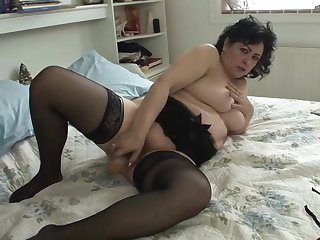 Chubby brunette in a black corset, Virginia is playing with her favorite dildo in the bedroom