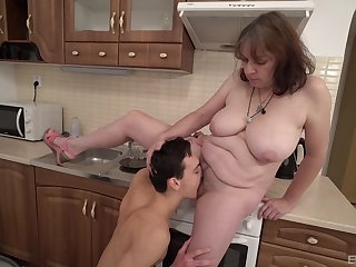 Dirty mature mommy drops on her knees to suck a younger dude's cock