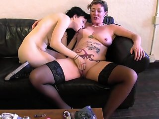 Old lady and a young lesbian lube up and fuck toys